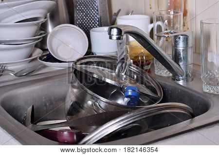 A Huge Pile Of Unwashed Dishes In The Kitchen Sink And On The Countertop