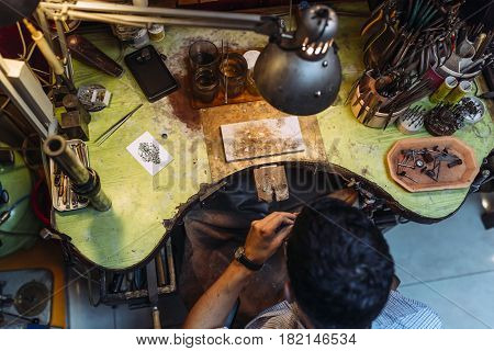 Craftsman working on workbench surrounded by his tools