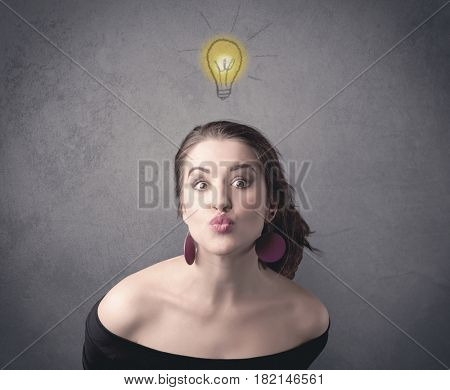 A teen student girl with funny facial expression has a good idea illustrated by a drawn light bulb lighting up above the head on the grey wall background concept.
