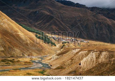 Riverside of Terek against the village on the hill in Greater Caucasus Mountains in Kazbegi in autumn Georgia.
