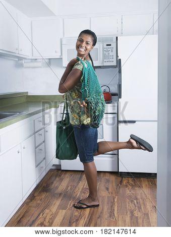 Mixed race woman holding reusable grocery bag