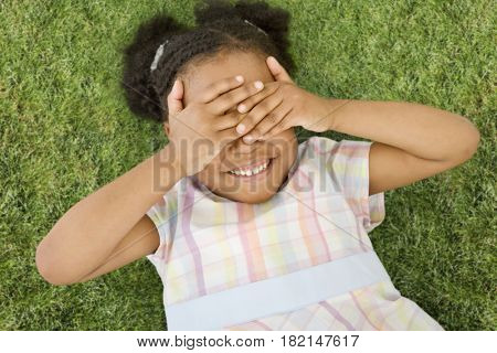 African girl laying in grass with eyes covered