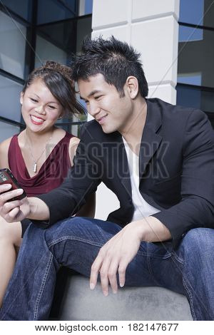 Asian man showing cell phone to girlfriend
