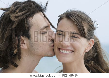 Hispanic man kissing girlfriend