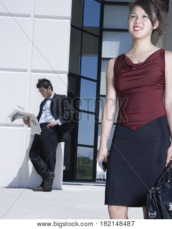 Asian businesswoman standing outdoors with briefcase