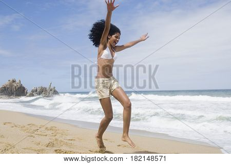 African woman jumping at beach