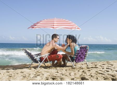 Multi-ethnic couple relaxing at beach