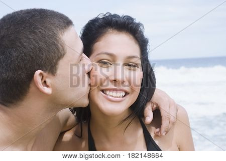 Hispanic teenager kissing his girlfriend