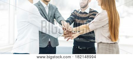 friendly business team standing in a circle and joining his hands together