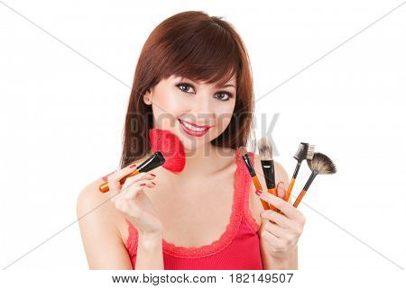 Young woman with brushes for make-up isolated on white background. Care for beautiful woman skin. Makeup at beauty salon. Closeup portrait of smiling woman face