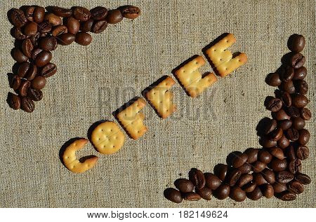 Coffee. The Word From The Edible Letters Lies On The Gray Canvas With Coffee Beans