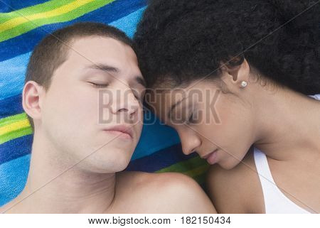 Multi-ethnic couple sleeping at beach