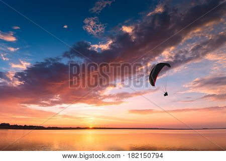 Silhouette Of Flying Paraglide Over The Sea Sunset
