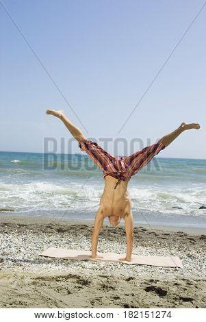 Hispanic man doing handstand on beach