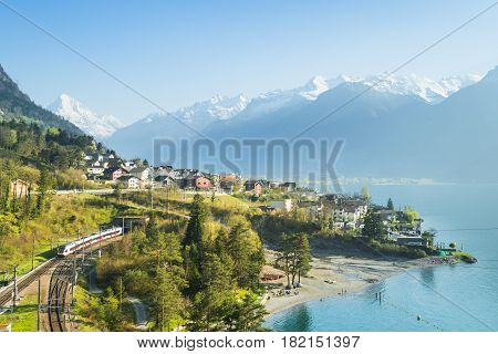 View of the small town in the Alps mountains. Railway along Lake Lucerne. Canton of Uri.