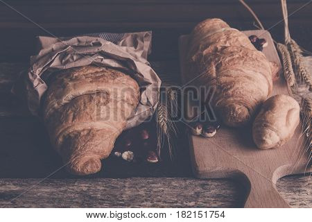 Croissants With Chocolate On Board Near Wheat On Wooden Sackcloth Background. Rustic Style. Toned Ph