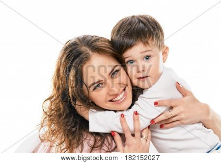 Cute smiling little boy embracing his happy mother on white background