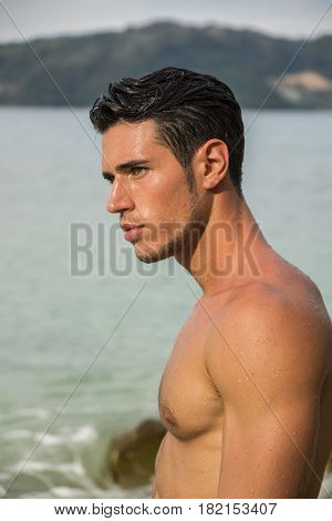Attractive young man in the sea getting out of water with wet hair, looking away to a side. Profile view
