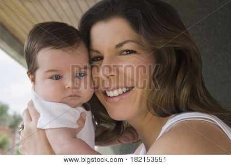 Smiling Hispanic woman holding baby