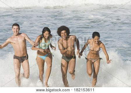 Multi-ethnic friends running in surf at beach