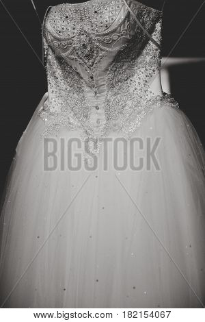 Gorgeous bride's dress with corset embroidered with jewels hang in the dark room