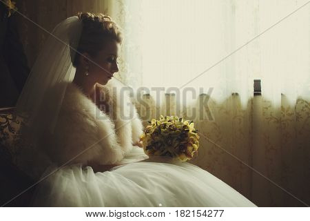 Thoughtful Bride Sits In A Chair Behind A Window Holding A Wedding Bouqet On Her Skirt