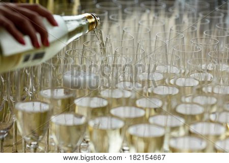 Waiter pours champagne in the wide glasses
