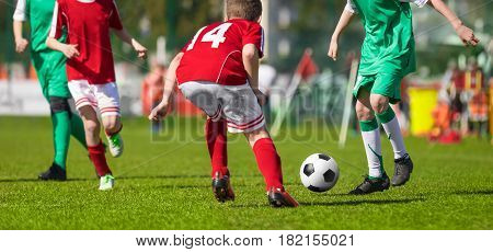 Football Soccer Match for Kids. Young Football Athletes. Coaching Youth Soccer. Children Playing Soccer Game Tournament. Boys Running and Kicking Football. Youth Soccer Coach in the Background