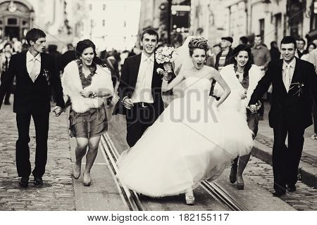 A balck and white picture with warlike bride walking with friends around the city square