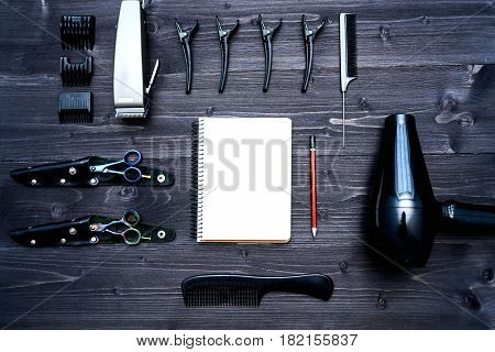 Hairdresser tools on wooden background. Blank card with barber tools flat lay. Top view on wooden table with scissors comb clipper and hairdryer with empty notebook and pencil free space. Barbershop manhood concept