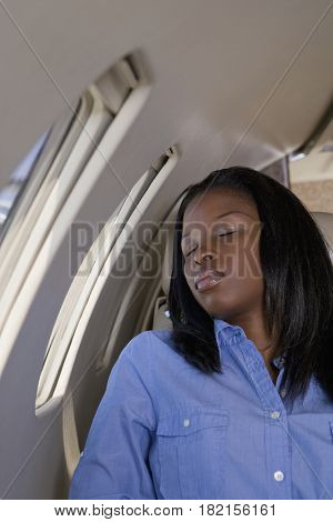 African businesswoman sleeping on private jet