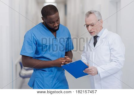Helping young generation. Aged qualified friendly doctor standing in the hospital while holding folder and consulting African American intern