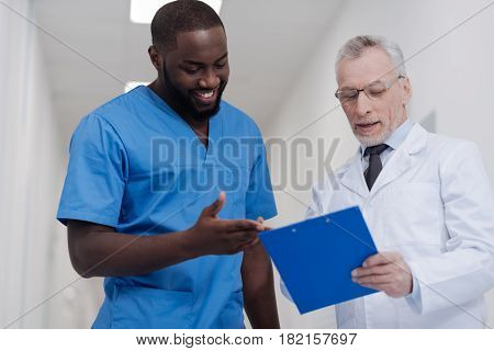 Sharing experience with young generation. Elderly professional bearded doctor standing in the clinic while holding folder and having conversation with African American intern