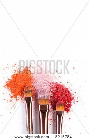 Makeup brushes closeup with blush or eyeshadow of pink, red and coral tones sprinkled on white. Make up and female cosmetics background