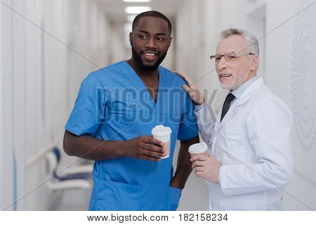 Conversation with reliable young colleague . Delighted professional aging doctor standing in the clinic while holding cup of coffee and enjoying conversation with African American colleague