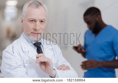 Ready to give useful advise. Confident proficient senior physician standing in the clinic and holding glasses while African American colleague using gadget in the background