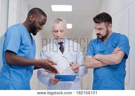 Always happy to share opinions. Easygoing bearded aging doctor standing in the hospital while holding the folder and having conversation with young colleagues