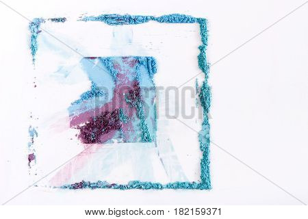 Makeup eyeshadow and blush abstract background of pink, blue and coral tones sprinkled on white. Make up and female cosmetics background