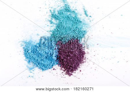 Makeup splash, cosmetics background. Eyeshadow crushed palette, blue and violet colorful powder on white, art of make-up