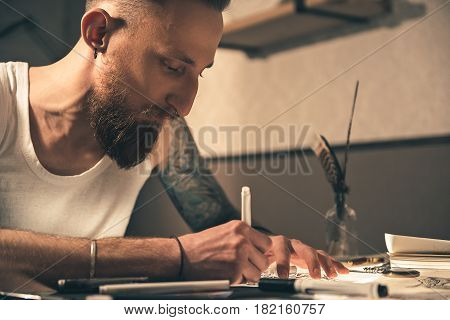Low angle side view of serious man creating pictures in tattoo salon. He locating at desk
