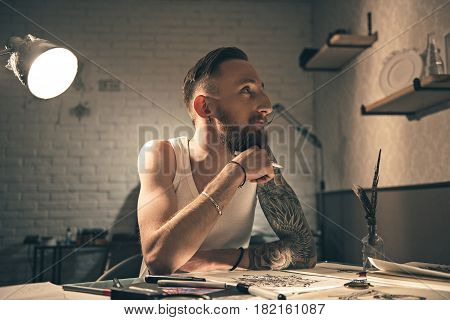 What I want to draw. Man expressing thoughtfulness while making tattoo images. He locating at desk