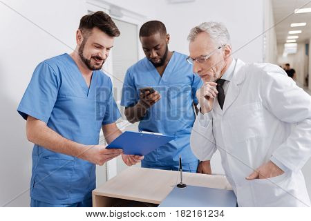 Specifying exact details. Involved smart old mentor working in the hospital and checking everyday report while having conversation with interns