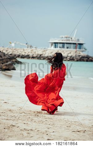 Beautiful young woman with long hair in red dress goes along the beach. Girl in red dress. Long red dress flutters in the wind