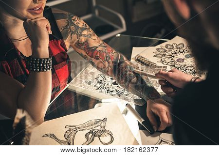 woman arm with tattoo images. Man asking significance of her arts. They sitting at table