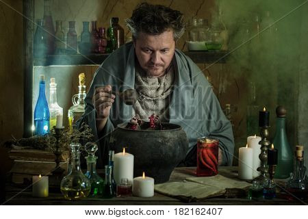 the wizard brews a potion in interior