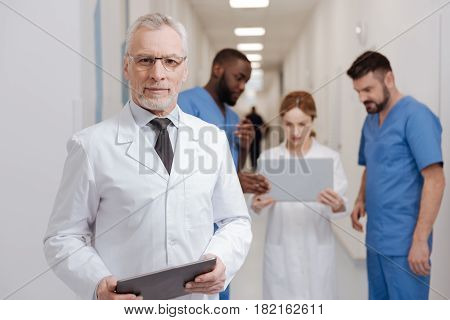 The epoch of modern technologies. Charismatic bearded amused pediatrician enjoying job in the clinic and holding tablet while other colleagues working with laptop in the background