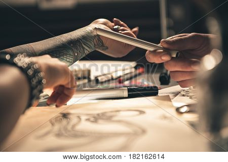 close up woman arm with tattoo leaning on table. Man asking about her images
