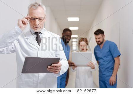 Practicing new approach. Senior bearded involved pediatrician enjoying job in the clinic and working with tablet while other colleagues using laptop in the background