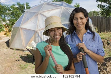 Mother and daughter gardening near conservatory
