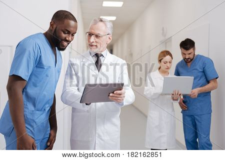 Just see the difference . Joyful skilled aging pediatrician enjoying job in the hospital and working with tablet while other colleagues using laptop in the background